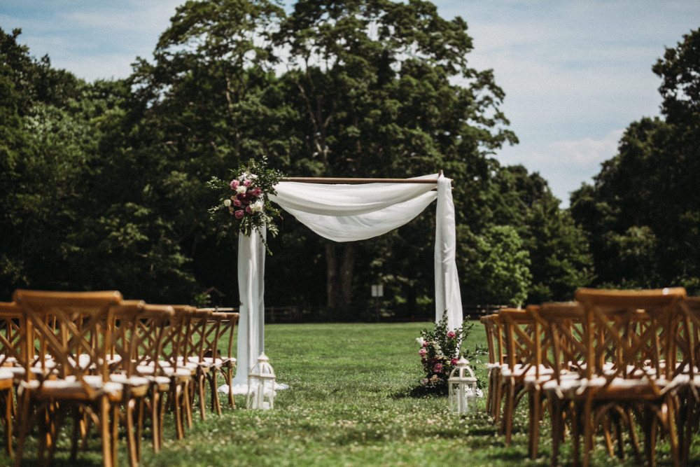 Simple ceremony arch with dusty rose, white, greenery flowers