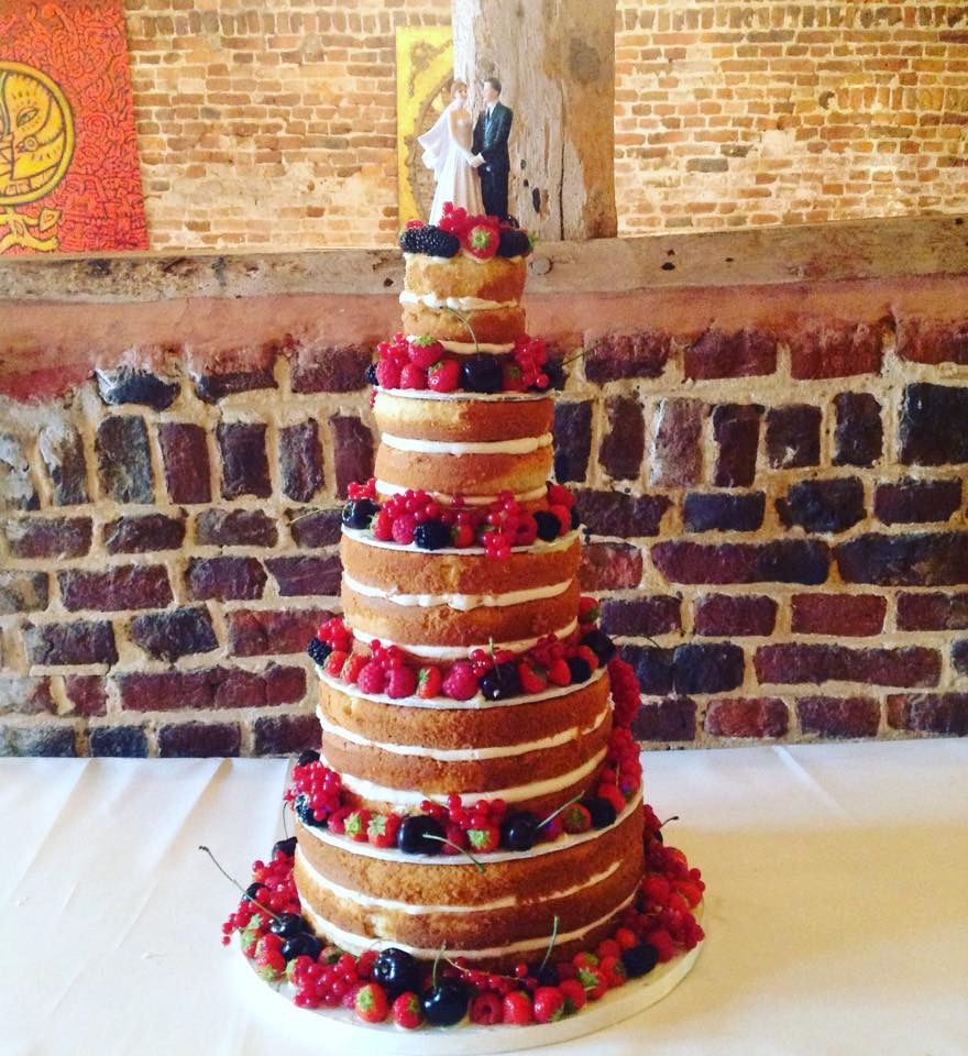 A fresh naked cake decorated with an abundance of red fruits and mint leaves.