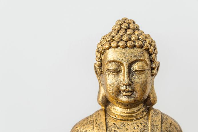 Generic golden statue of Buddha on white