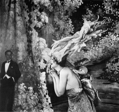Lartigue (1894-1986) captured the intimate moments of Paris amid moments of change throughout the 20th century. Here he produced an image of a cabaret singer in her element amid the lush trappings of her stage set, appealing to the affections of an unseen audience as a waiter impasssively looks on, complicating the world created on the stage and its interactions with reality.