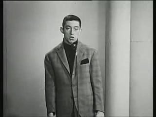 An early performance of Serge Gainsbourg in his element, a Parisian supper club where he is initially presented by a fashionable young hostess. His song, about the (perhaps suicide-inducing) tedium of the life of ticket puncher who works at a train station in Paris, explains his somehwat combative, emotional, standoffish demeanor among the suave diners of the club, who nonetheless have attended to consume his rendition of the inner life of a quotidian occurence.