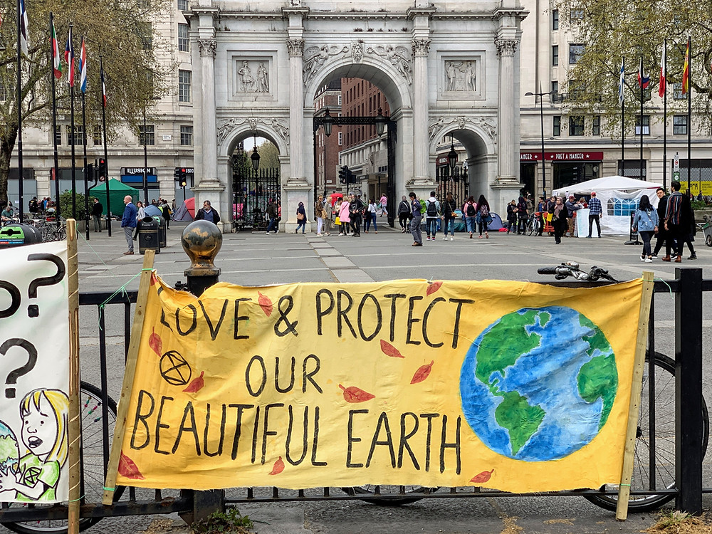 """Poster that says """"Love & protect our beautiful earth"""" at Marble Arch, London"""