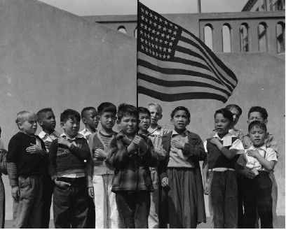 San Francisco, California. Flag of allegiance pledge at Raphael Weill Public School, Geary and Buchanan Streets. Children in families of Japanese ancestry were evacuated with their parents and will be housed for the duration in War Relocation Authority centers where facilities will be provided for them to continue their education, 1942
