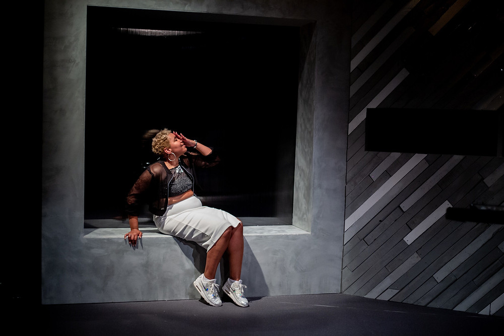 Black woman with short blonde hair and white skirt sits on an industrial grey frame