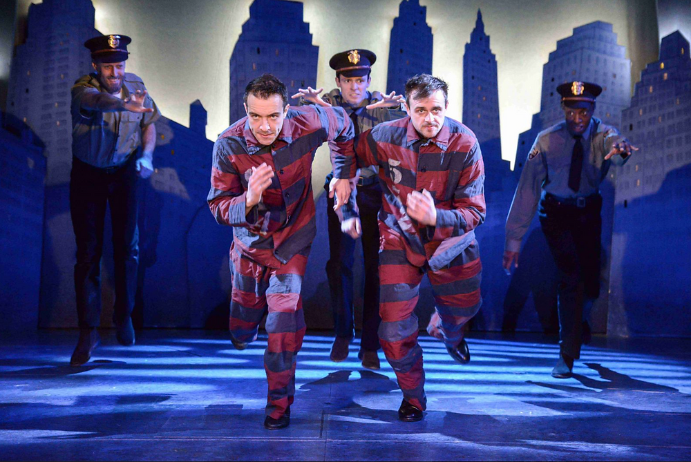 Two white men in red and blue striped prison uniform run from three police officers, hands outstretched in a musical esque way