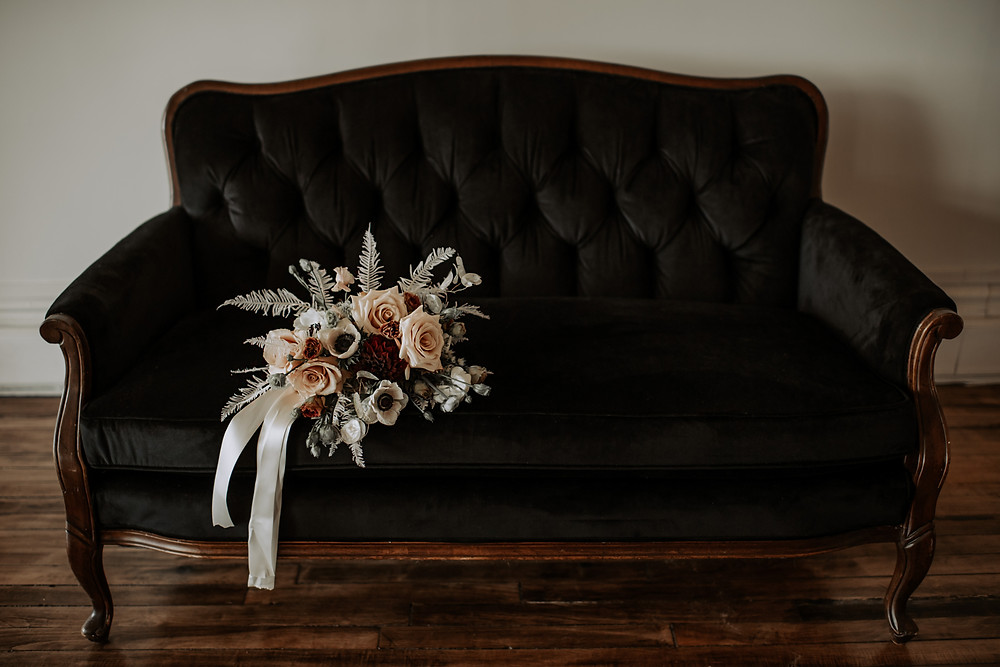 Black settee with fall wedding bouquet