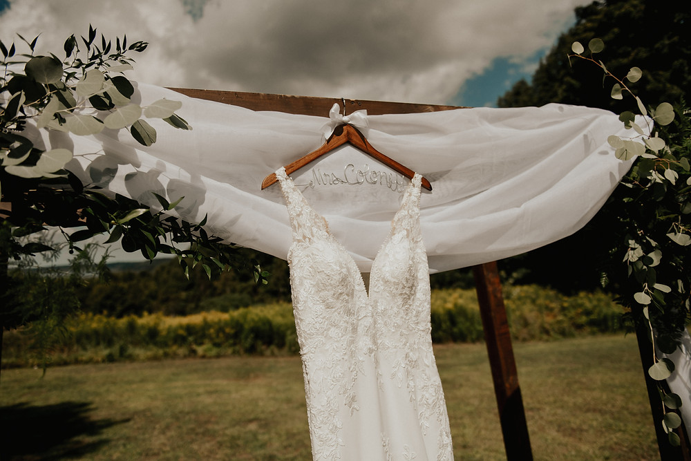 Wedding dress hanging on arbor for outdoor wedding ceremony