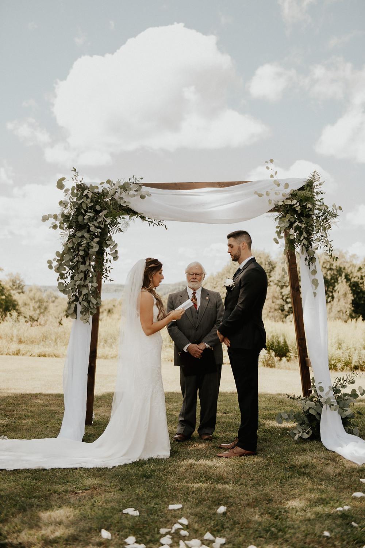 Arbor wedding backdrop with white linens and eucalyptus
