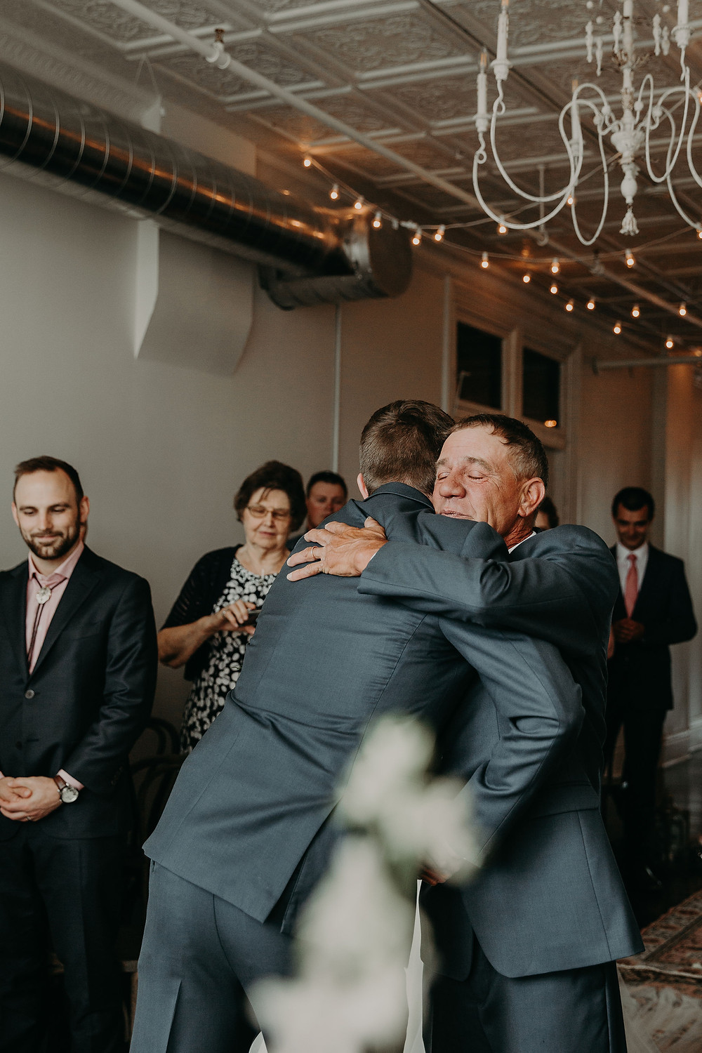 Father of the bride hugging groom: Summer Small Wedding at The Lincoln Loft by Pretty Little Vintage Co.