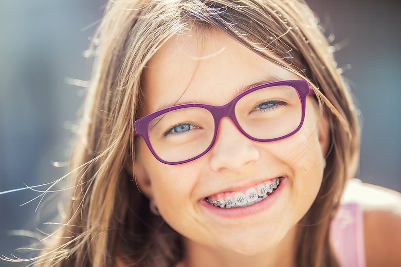 Happy smiling girl with dental braces an