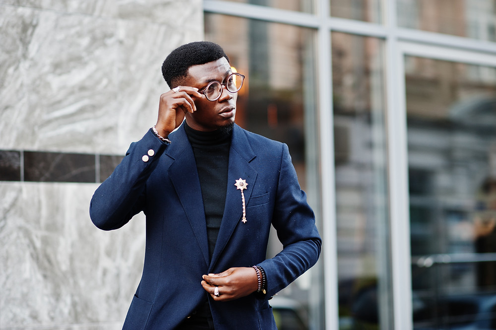 A dapper black man dressed in a navy blue suit with black tshirt and gold accessories