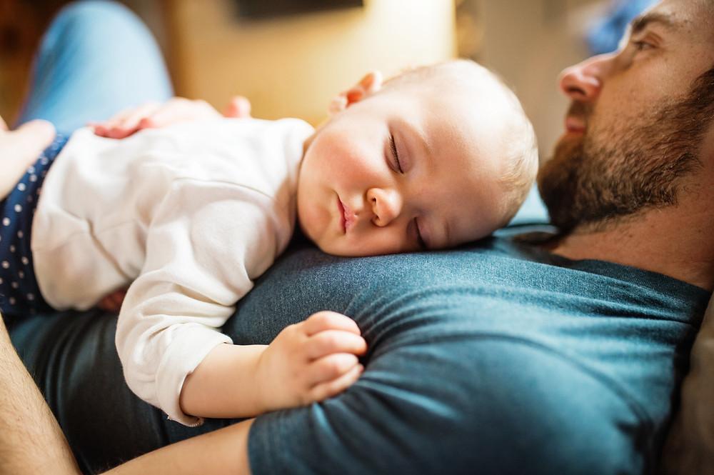 bebê dormindo no peito do pai