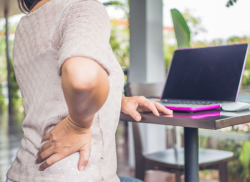 Woman with Lower back pain in Debary is sitting at a computer