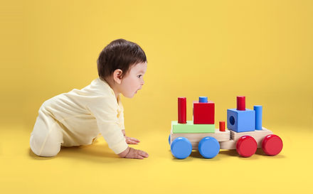 A baby playing with a toy train
