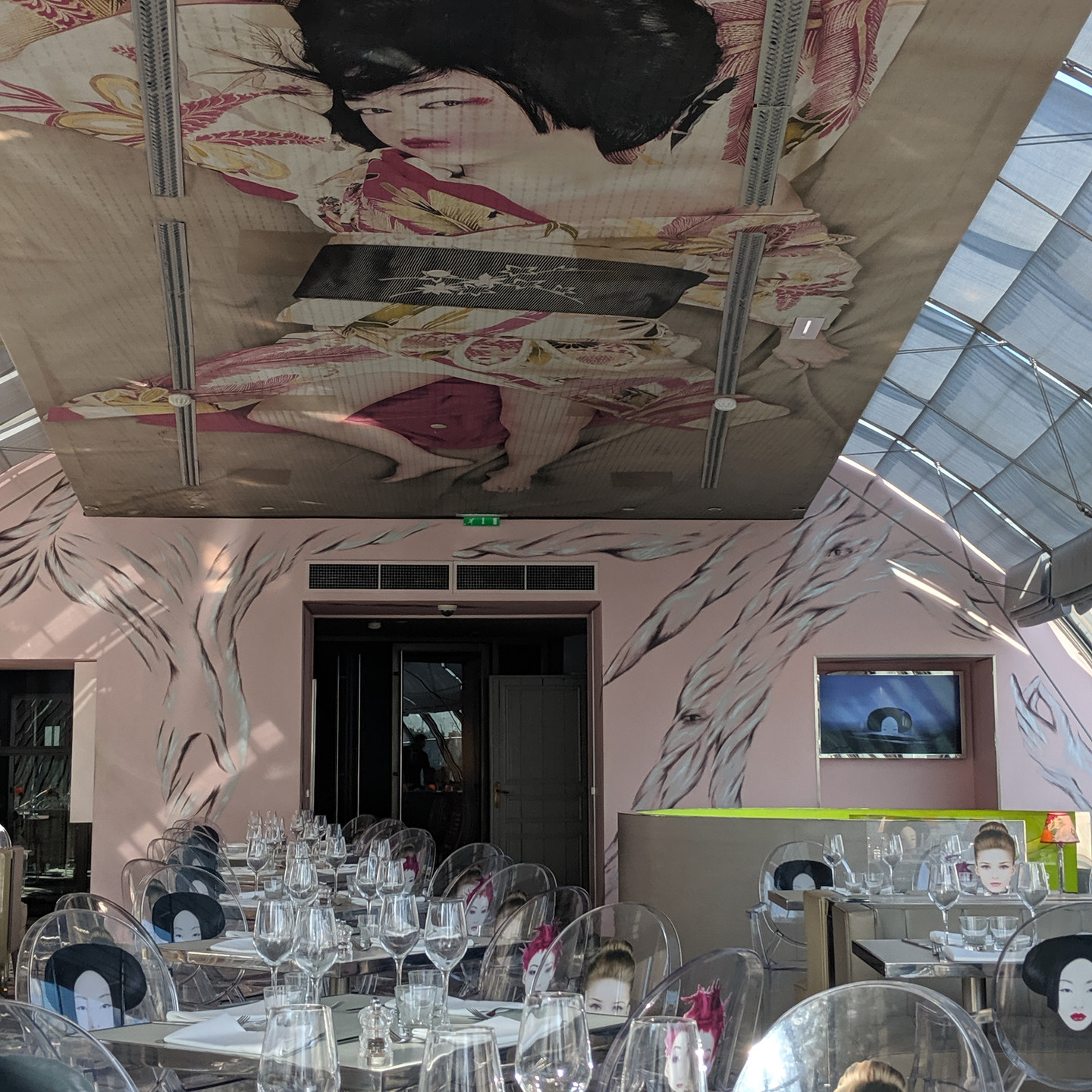 Kong Restaurant in Paris featuring Glass Barrel Ceiling and Lucite Chairs with Faces Printed on The Backs