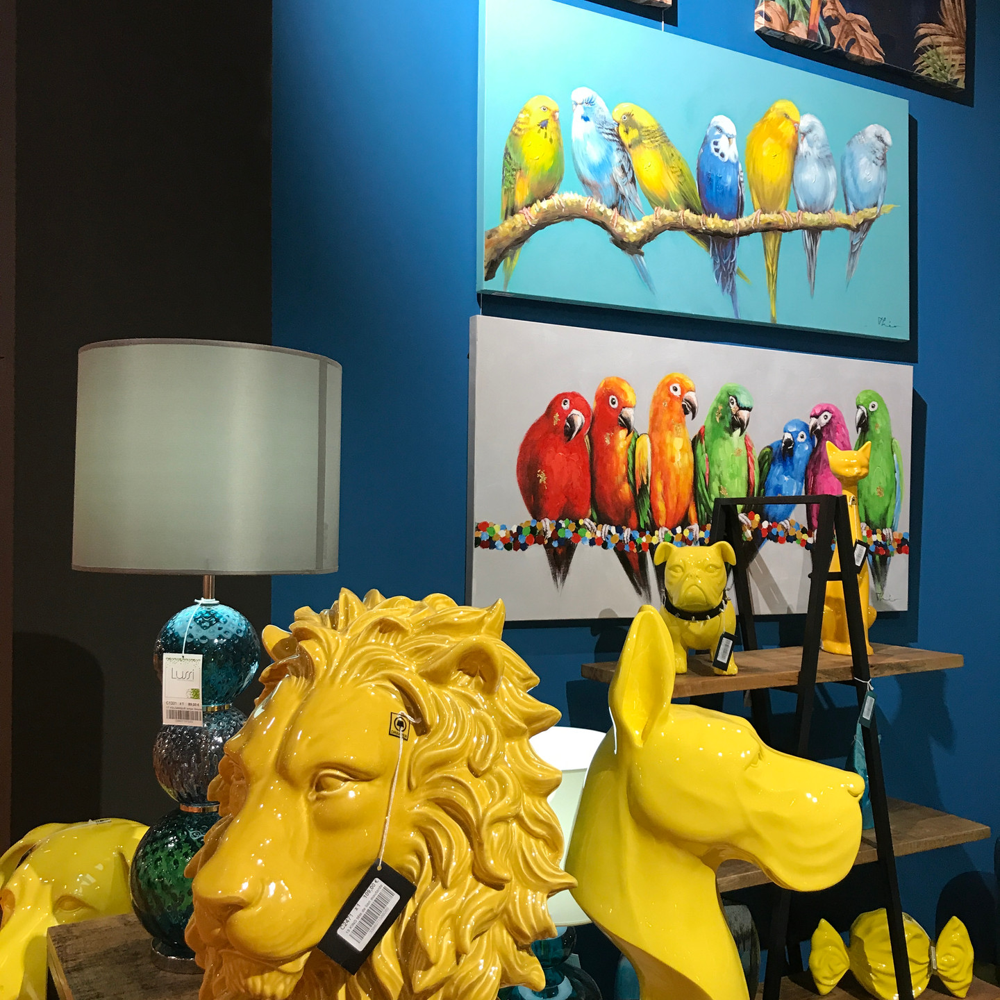 Yellow Lion and Dog Head Sculptures with Bright Blue Wall and Brightly Colored Parrot Artwork