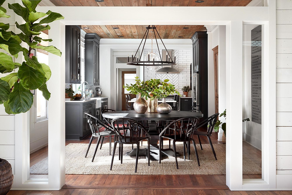 Black & White Farmhouse Style Kitchen and Dining Room with Jute Rug Round Dining Table and Round Iron Chandelier with House Plants