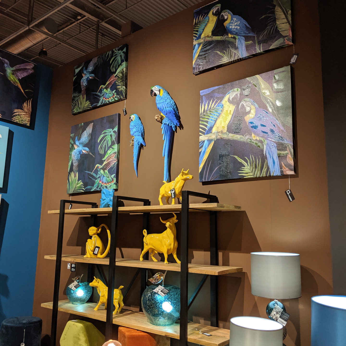 Blue and Yellow Animal Statues on Shelf with Parrot Paintings