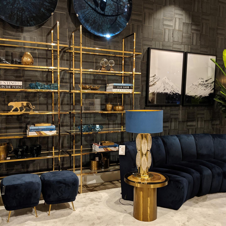 Round Navy Velvet Sofa with Brass Wall Shelves and Brass Table Lamp with Blue Velvet Shade