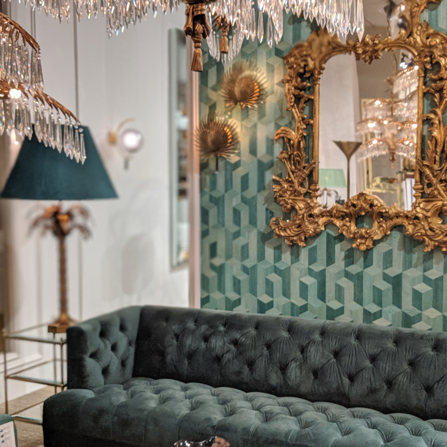Green Velvet Eichholtz Sofa with Green Wallpaper, Gilded Wall Mirror, and Crystal Palm Tree Inspired Chandelier