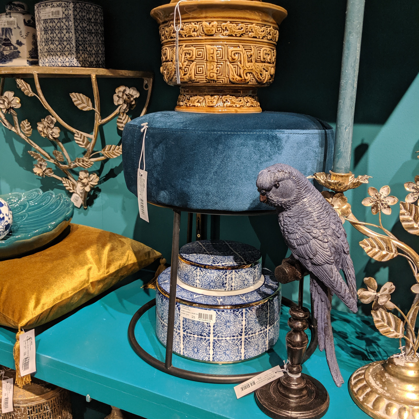 Peacock Blue Home Decor Display with Velvet Stool, Mustard Yellow Velvet Pillow and Carved Parrot Statue