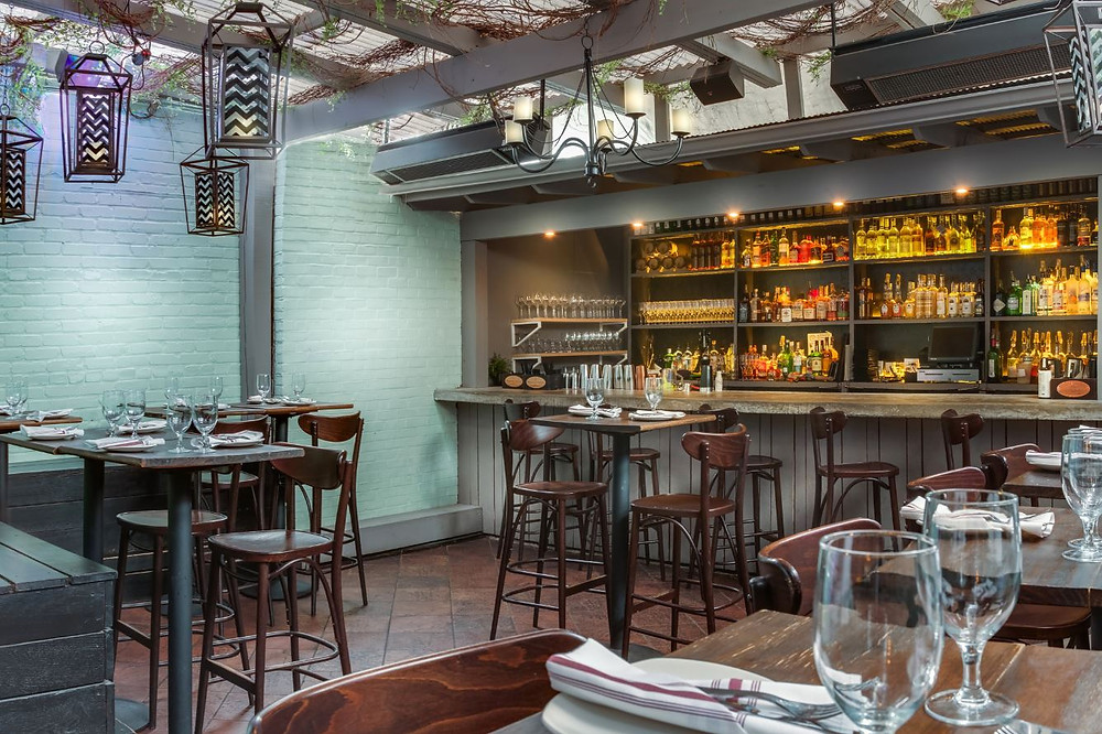 Ambar Washington DC Balkan Restaurant back patio with aqua brick walls, hanging lanterns, chandelier, and concrete bar