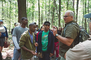 An older man showing a group of young adults something in a forest
