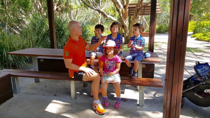 Dr Ces Colagrande - happy kids at park bench