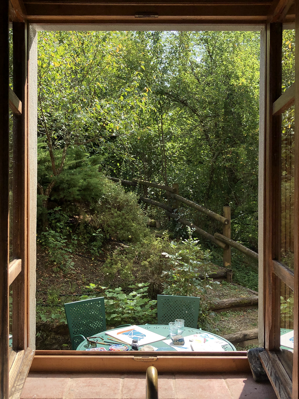 View of a window showing a a green metal table outside on the countryside
