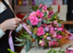 Woman making a bouquet of roses, tying t