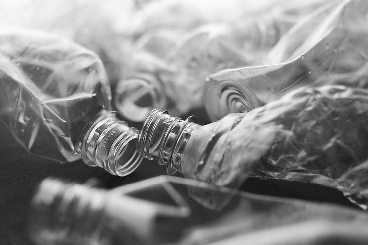 Crushed and abandoned plastic bottle on black background .jpg