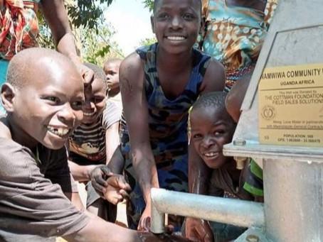 Moradores de uma comunidade carente em Uganda festejam a chegada de água potável