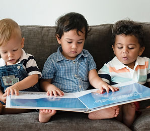 Three little boys reading a book on a so
