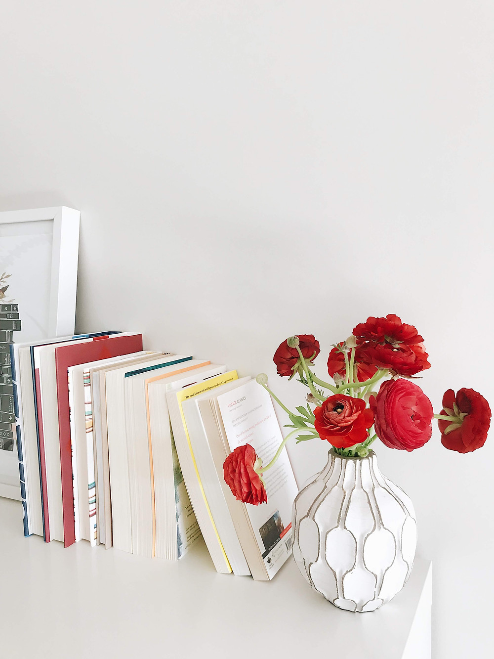 a bookshelf featuring books and flowers