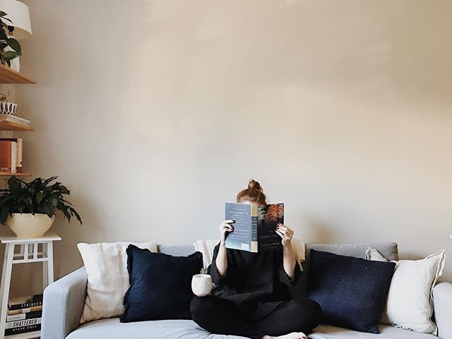 portrait of a woman reading a book on a couch with coffee