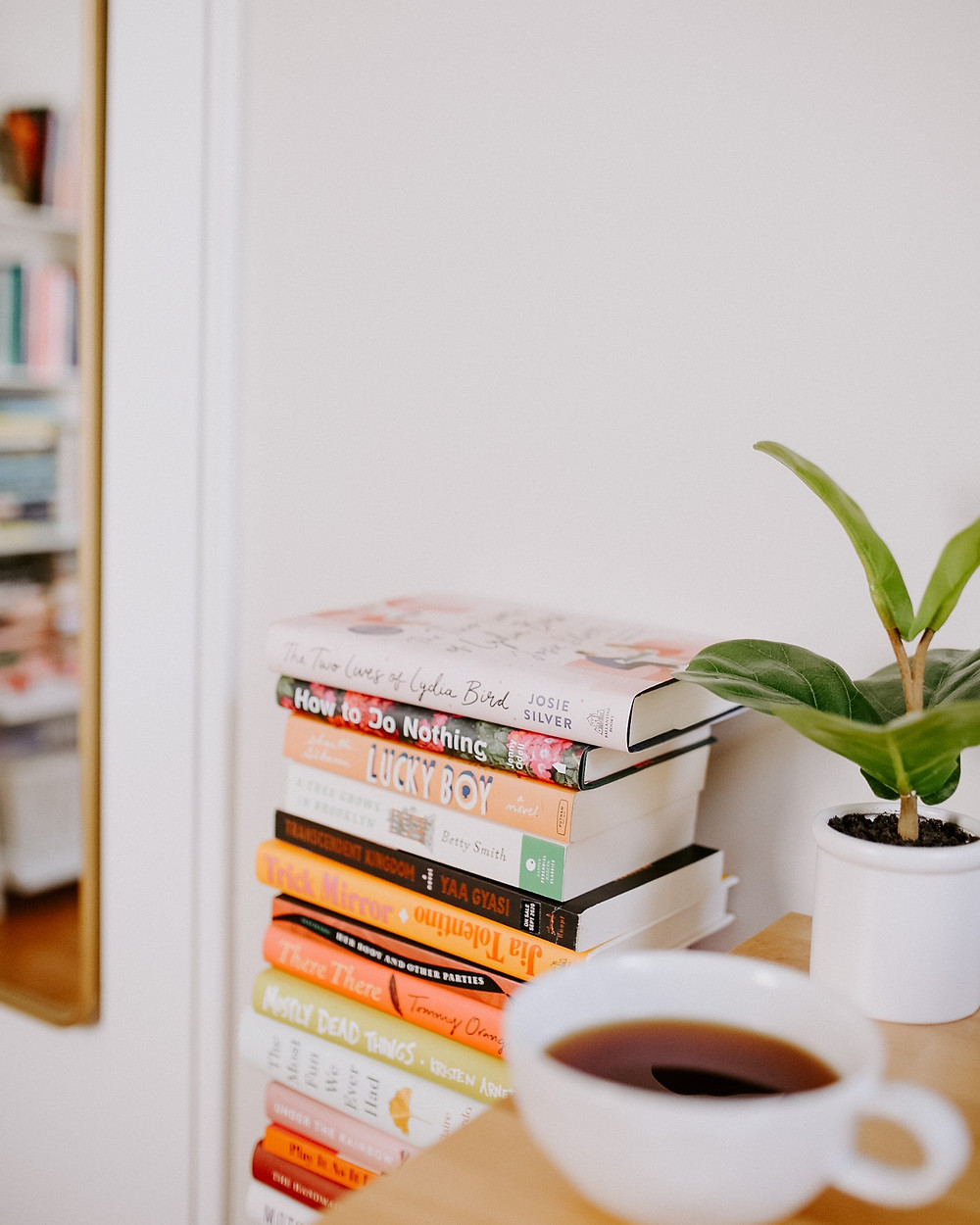 A stack of books with coffee and plants