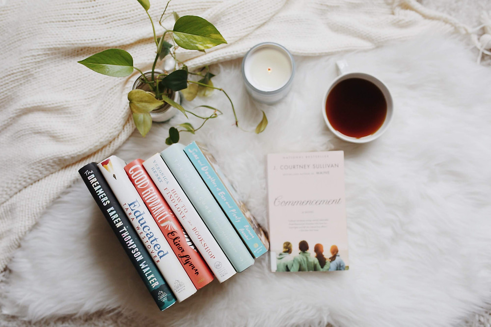books on a white blanket with coffee, a candle, and plants