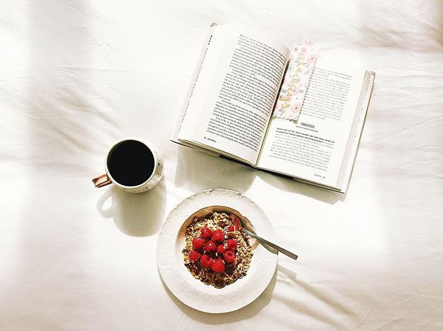 overhead shot of breakfast with a book and coffee on a white background