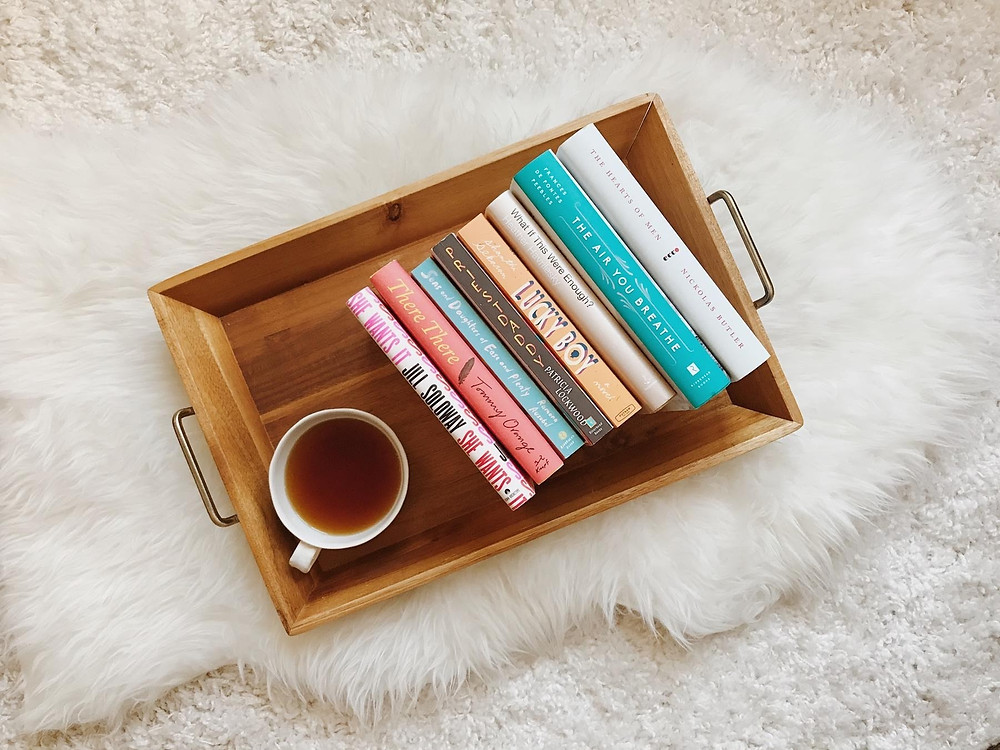 Overhead photograph of book stacks on a tray with coffee on a white background