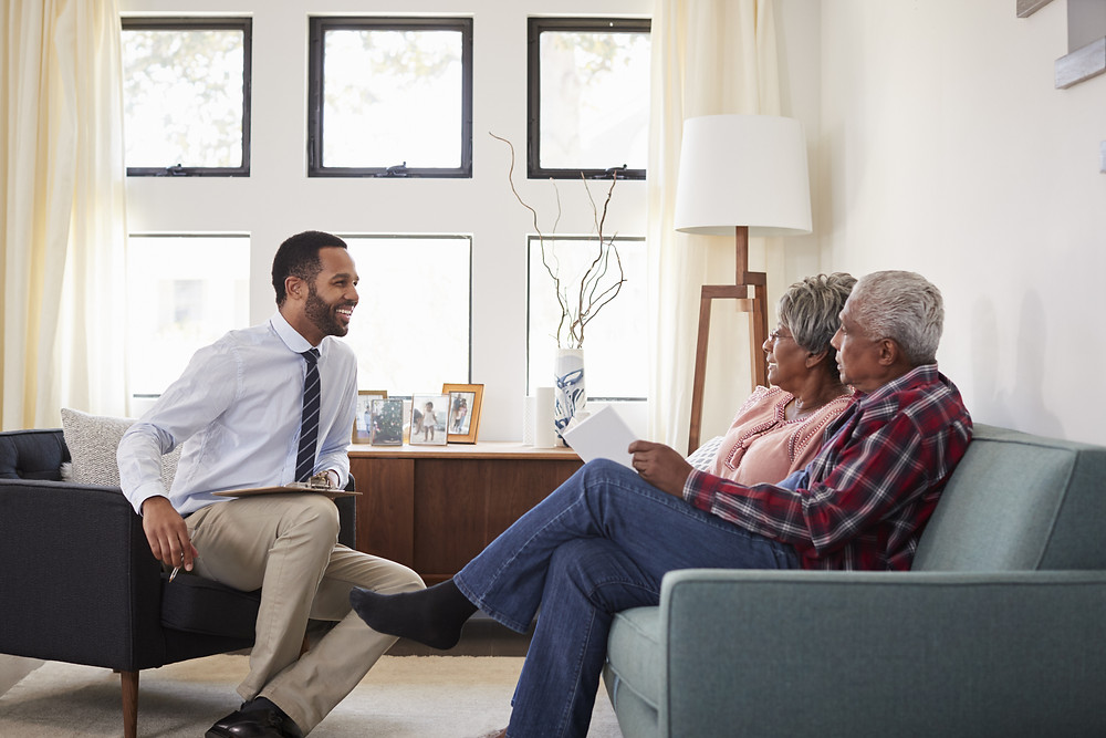 insurance agent meets with elderly couple to review their policies and make sure they're protected