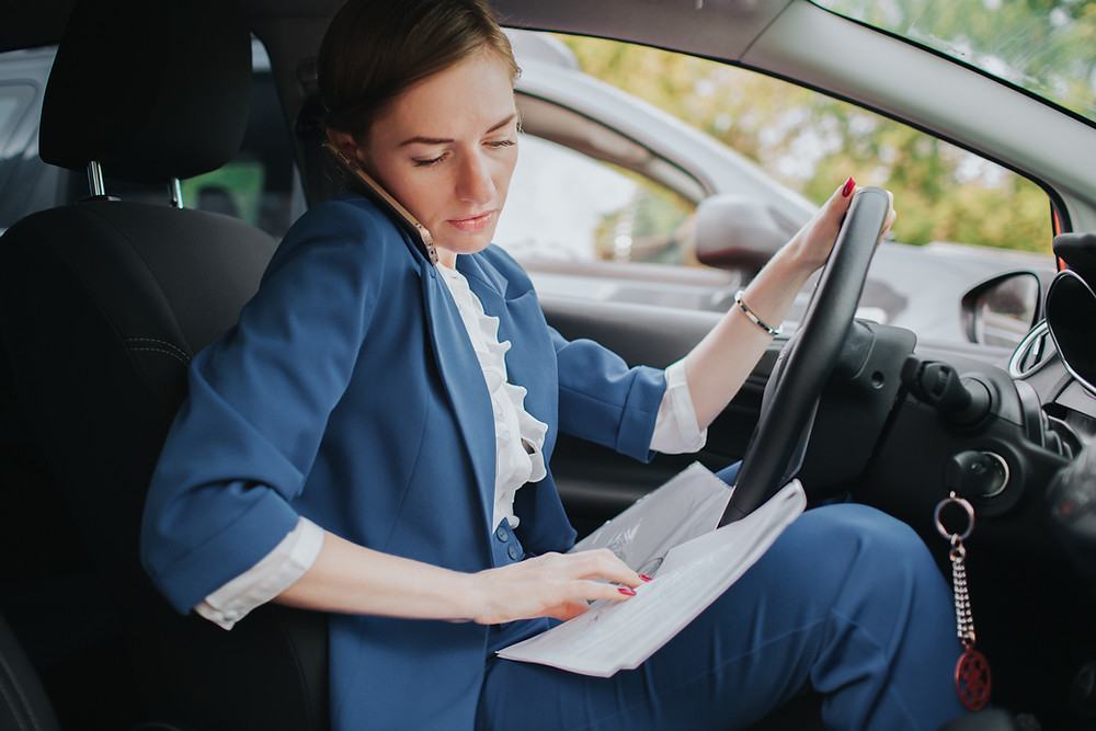 Busy businesswoman takes a call while she's in the car.