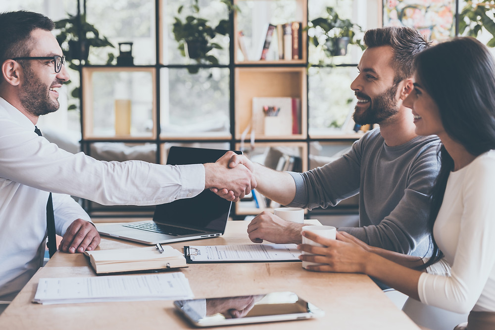 Insurance agent shakes hands with his clients as he meets with them.