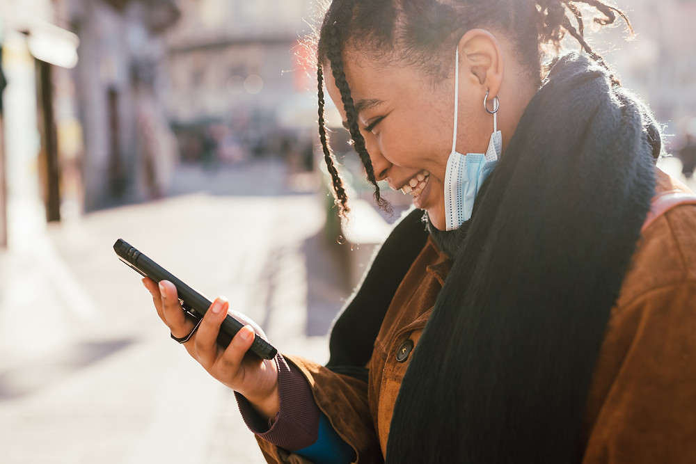 Young woman smiles at her smart phone.