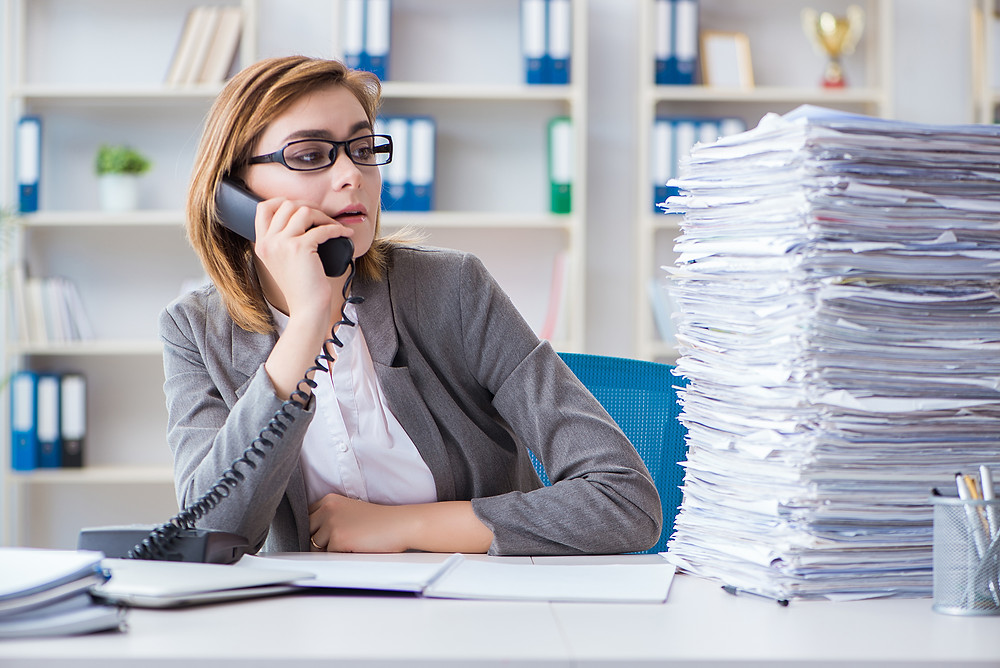 Insurance staff member on the phone while staring at the large stack of paperwork she still has to do.