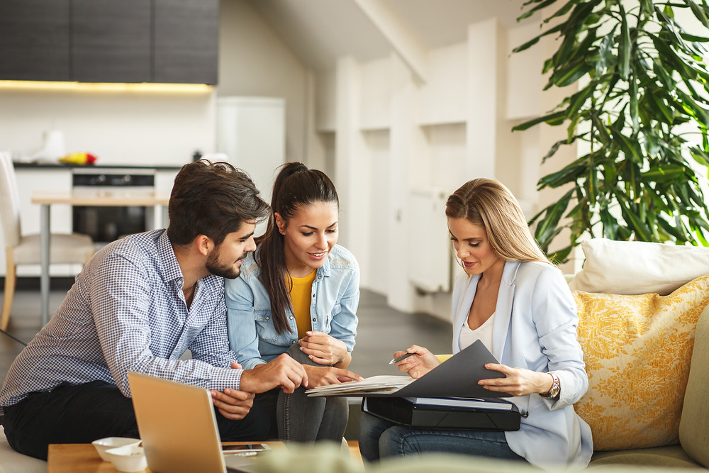 Newly wed couple meets with their insurance agent to review policies and reduce risk.
