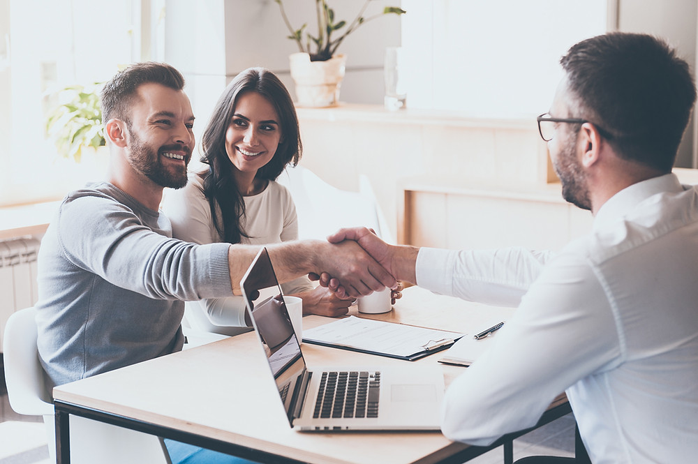 Insurance customer shakes hand with his agent after a customer insurance review appointment.