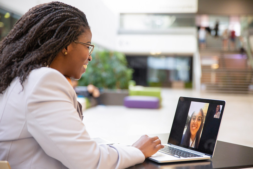 Insurance agent meets with client over video call on her laptop.