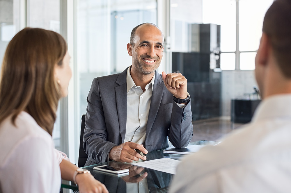 Insurnace agent sits with his clients to discuss their policies and help them reduce risk.