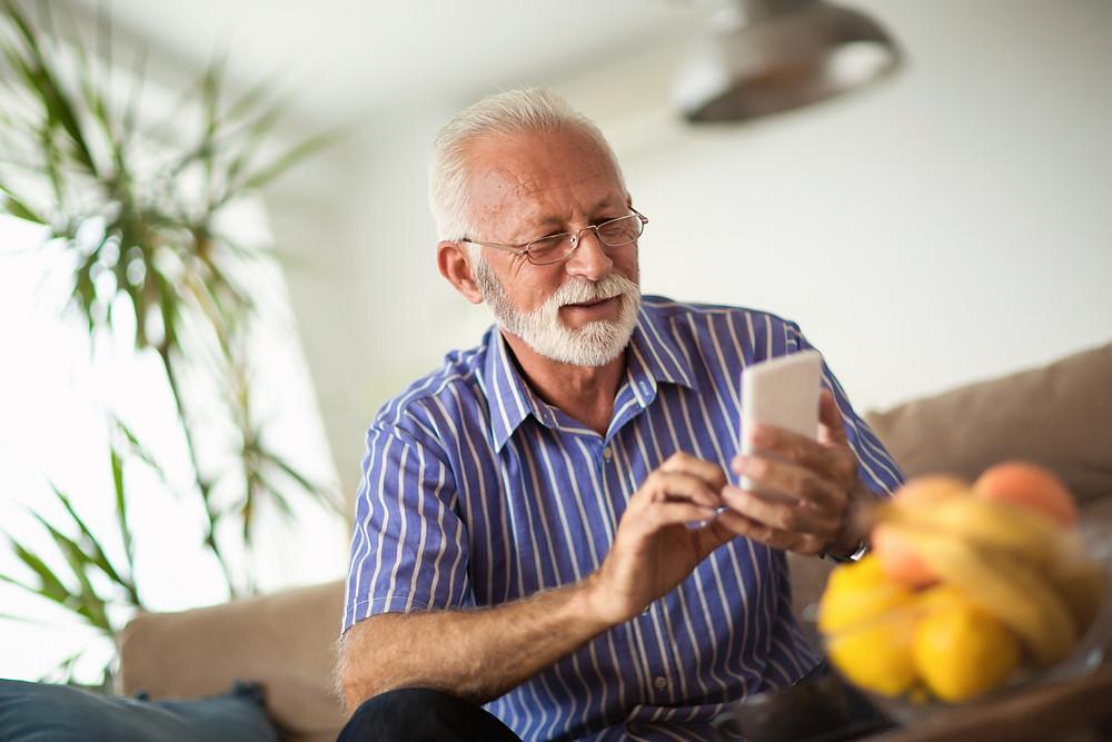 Elderly man looks at his phone.