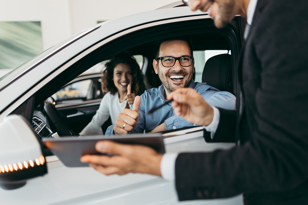 Insurance agent consults car salesman client about which car he should buy